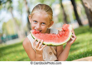 Kid with watermelon slice - Cute girl sitting in park and...