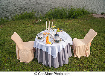 The fashionable holiday table outdoors on the banks of the...
