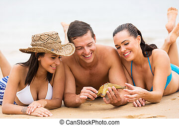 friends spending time together at beach - cheerful friends...