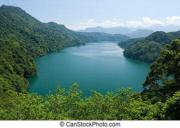 peaceful lake surround by forests and mountains. Asia,...