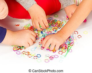 Colourful Loom Bands - Close-up of three children's hand...