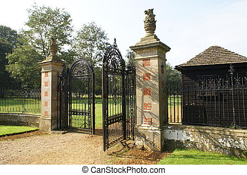 wrought iron gate with griffin statues on the gate posts