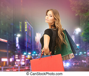 young happy woman with shopping bags over city - people,...