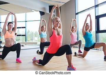 group of women making lunge exercise in gym - fitness,...