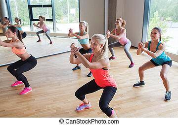 group of women making squats in gym - fitness, sport,...