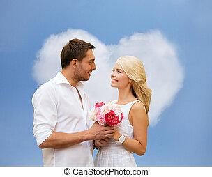 happy couple with flowers over heart shaped cloud -...