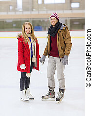 happy couple holding hands on skating rink - people,...