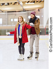 happy couple on skating rink - people, friendship, sport and...