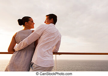 back view of young couple looking at each other on cruise