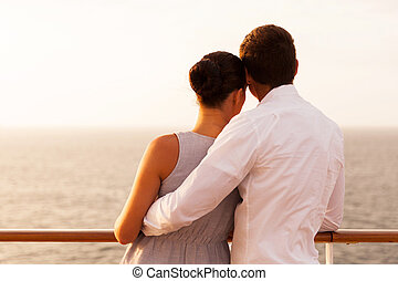 rear view of young couple on cruise vacation looking at the...