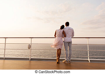 young couple standing on ship deck during sunset - rear view...