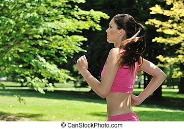 Young woman running in green park