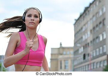 Young person listening misic running in city street - Person...