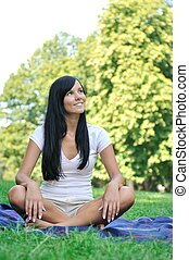 Young smiling woman sitting on rug in park