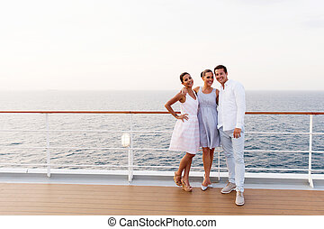 three friends standing on cruise ship deck - full length...