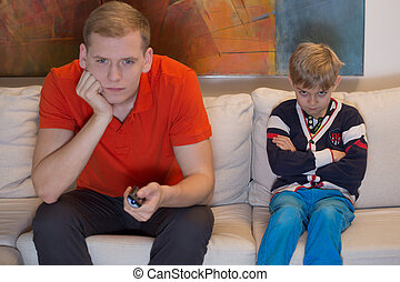 Immature dad watching tv and his bored son