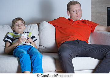 Child using smartphone - Child sitting on the sofa and using...