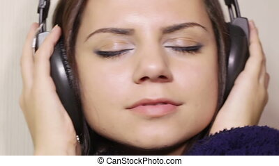 Girl bathrobe in headphones CU - Seated in the headphones...
