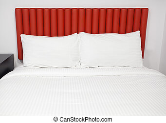 Bed with headboard and pillows in a hotel room