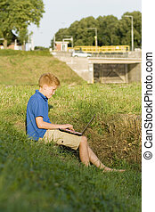boy at a watergate - young boy is sitting with a laptop at...