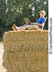 boy on a bale of straw