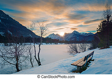 lonely park bench at sunset in alps with frozen lake in...