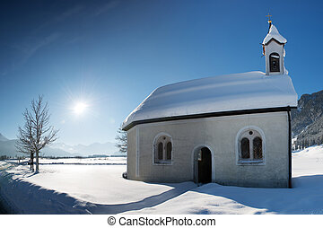 old chapel in winter snow landscape with sunlight and blue...