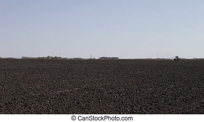 tractor plowing black field boundless on blue sky background