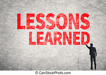 Lessons Learned - Asian business man write words on wall,...