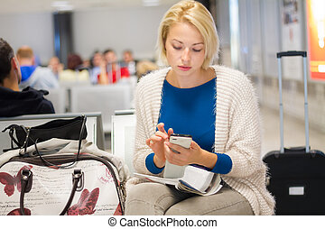 Woman using a cell phone while waiting - Casual blond young...