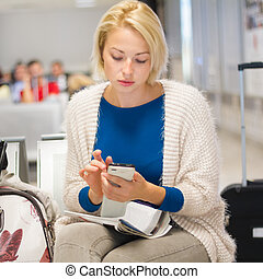 Woman using a cell phone while waiting. - Casual blond young...
