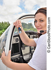 Pilot girl sitting in the cockpit and showing keys