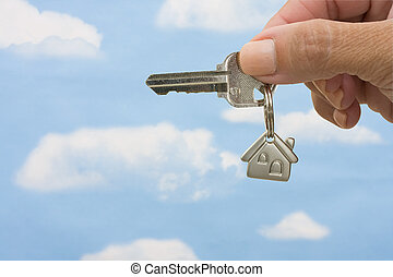 Unlocking Your Door - A key on a house keychain in a...