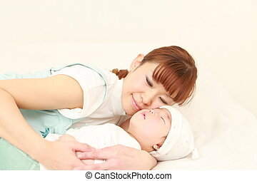 time to sleep - portrait of a young Japanese mom and her...