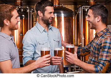 Cheers to friends! Three cheerful young men in casual wear talking to each other and smiling while holding glasses with beer and standing in brewery