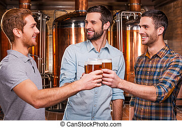 Cheers to us! Three cheerful young men in casual wear toasting with beer and smiling while standing in brewery in front of metal containers