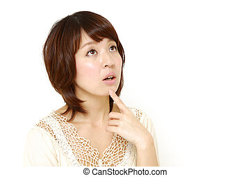 woman thinks about something - studio shot of young Japanese...