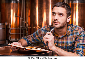 Generating ideas for his brewery Thoughtful young man in...