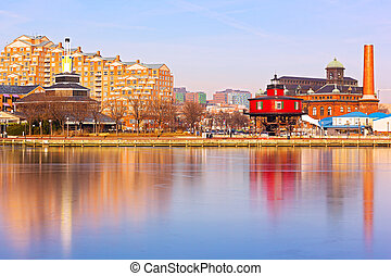 Baltimore waterfront buildings and the Seven Foot Knoll Lighthouse at sunset. Colorful reflections of waterfront buildings at Inner Harbor in Baltimore, Maryland.