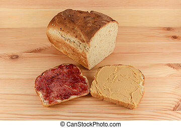Cut loaf of fresh bread with jelly and peanut butter slices...