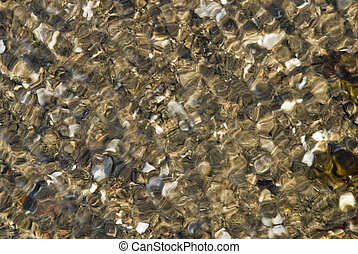 River pebbles in flowing water - River pebbles reflected by...