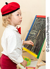 Cute child girl drawing chalk on easel in suit of artist in...