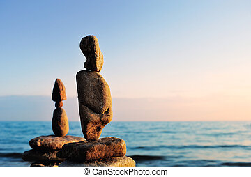 Elongated stones in balance on the seashore