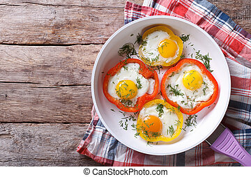 fried eggs in yellow and red peppers in a pan. top view