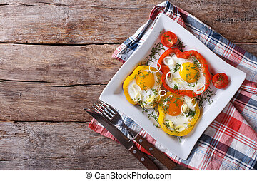 fried eggs in peppers on a plate. horizontal top view