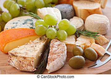 Various types of cheese and knife on wooden board