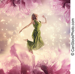 Beautiful young woman jumping on giant flower - Beautiful...