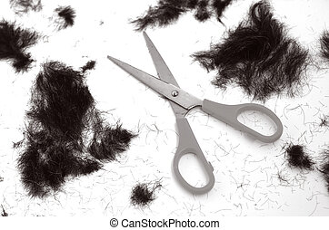 Trimmed hair on the floor with scissors. (BW) fashion...