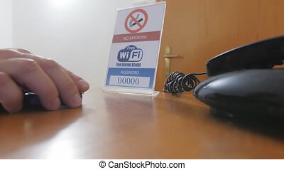 man logging internet hotel room - connecting to wifi network...