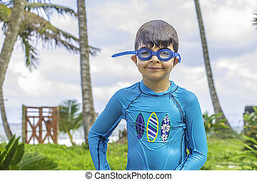 Swimming Boy - A young boy wearing swim goggles who is wet...